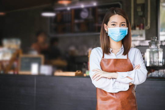 New normal startup small business Portrait of Asian woman barista wearing face mask working in coffee shop while social distancing.