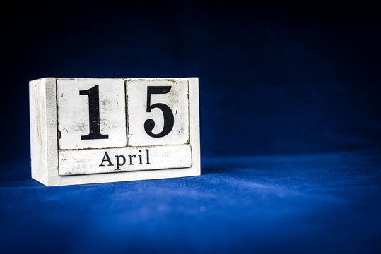 April 15th, Fifteenth of April, Day 15 of month April - rustic wooden white calendar blocks on dark blue background with empty space for text.