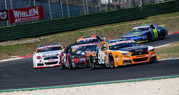 Group of Nascar cars challenging overtaking during Nascar Euro championship race