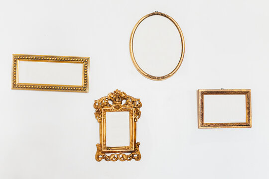 Empty Golden Frames on a White Wall