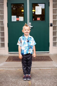 Boy with mohawk wearing Hawaiian shirt on first day of Kindergarten