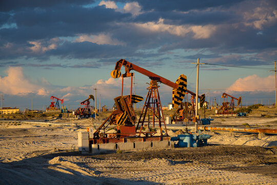 Oil Industry: Pumpjack on the oilfield at sunset