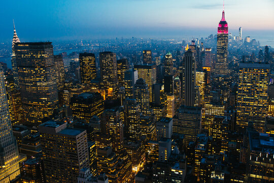 Aerial view of New York city at dusk - night with illuminated buildings in Manhattan and view of the Empire State