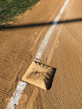 Detail of first base and freshly painted boundary line on baseball field