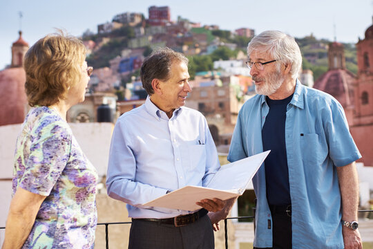 Older man talking to local real estate agent in colonial city