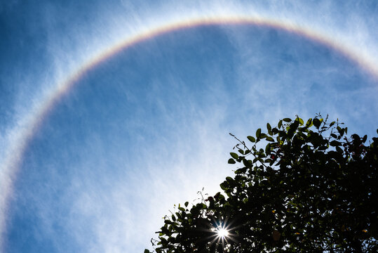 Big solar halo on a blue sky with strange clouds produced by light with ice crystals suspended in the atmosphere.