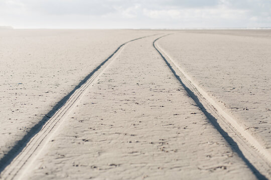 Marks of a vehicle on a empty beach.