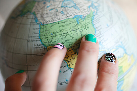 close up of world map / globe with fingers pointing to United States of America
