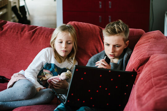 Siblings watching a movie on a laptop