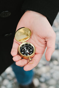 hand holding compass at beach