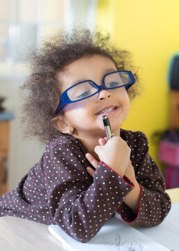 Portrait of a toddler wearing blue glasses sitting studiously as she scribbles and writes on a notepad