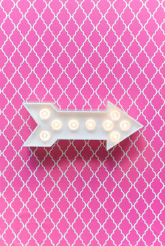 Arrow marquee light on a pink background.