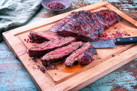 Barbecue wagyu bavette beef steak with red wine salt offered as close-up on a rustic wooden board