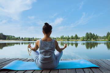 A young woman sits on a mat on a wooden pier in a lotus position with a rosary in her hands. Back view. Meditation, yoga in nature.