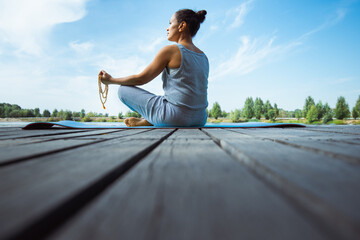 A young woman sits on a mat on a wooden pier in a lotus position with a rosary in her hands. Back view. Against the background of the blue sky. Meditation, yoga in nature.