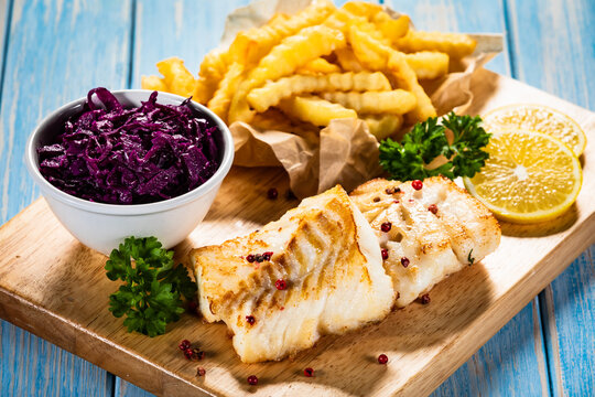 Fish dish - fried cod fillet with curly french fries and vegetable salad on wooden table