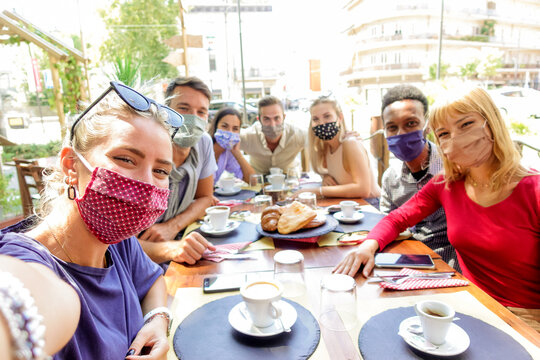 Multiracial group of friends wearing protection mask at the restaurant. Happy people celebrating having fan at coffee shop. New normal concept.