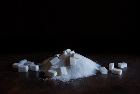 white sugar cubes and powdered sugar on an old iron table