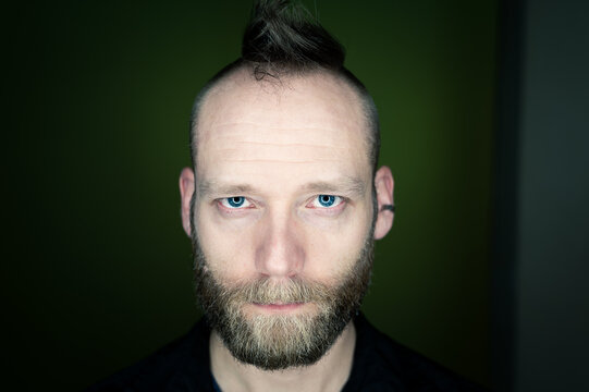 Man with beard and mohawk looks seriously at the camera.