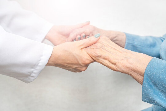 Helping and care for the elderly concept.Young nurse hands holding an old hands of senior woman.