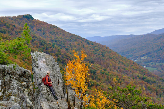 A hiker woman holds her camera and looks down the valley from the top of Seneca Rocks hike in West Virginia with a cloudy sky and fall trees