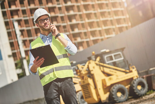 Important call. Young civil engineer or construction supervisor wearing helmet talking by phone while inspecting building site