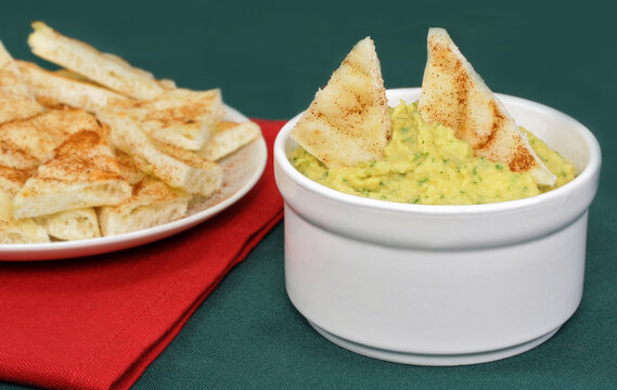 Hummus with naan bread in dip and on the side.
