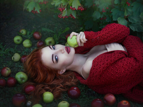 Young attractive beautiful red-haired woman with apples and Rowan berries in a fairy light. Art processing.