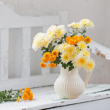 yellow chrysanthemums in jug on old  white wooden bench