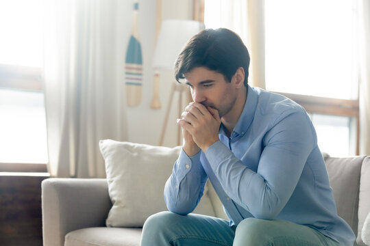 What should I do. Pensive sad millennial guy sitting alone on sofa in living room leaning forward clasping hands at chin lost in serious unhappy thoughts, looking for way out of difficult situation
