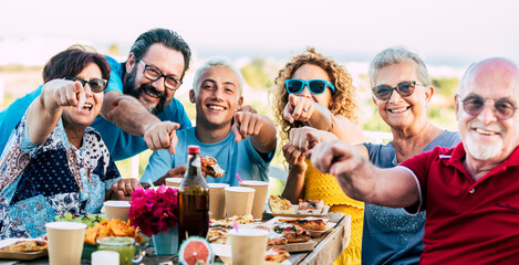 Photo sur Plexiglas Dinosaurs focus on hands - group of mixed ages family friends people enjoy and have fun together celebrating outdoor with table and food and drinks - cheerful caucasian men and women celebrating