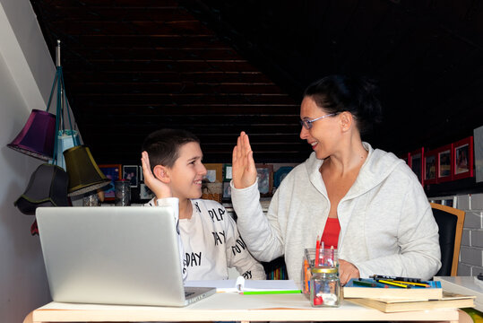 Mother and son home schooling, tutoring; home study, exploring internet and doing homework together