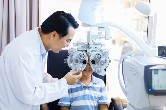 An Asian male doctor examines a child's vision. optometrists man are examining pediatric patients' eyes with the Autorefractor in a clinic.