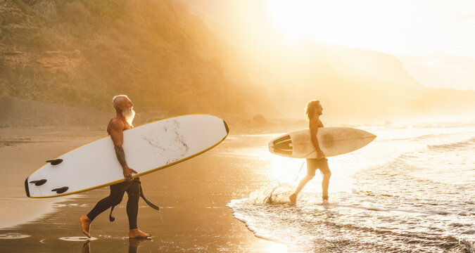 Happy friends with different age surfing together on tropical ocean - Sporty people having fun during vacation surf day - Elderly and youth people sport lifestyle concept