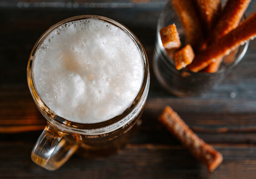 alcoholic drink, 1 beer with foam, croutons on a dark background top view,