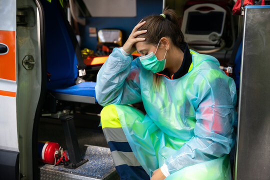 Portrait of a young woman doctor sitting on the ambulance resting exhausted where a first aid intervention during the Covid-19 pandemic, Coronavirus wearing a face mask - Rescue concept