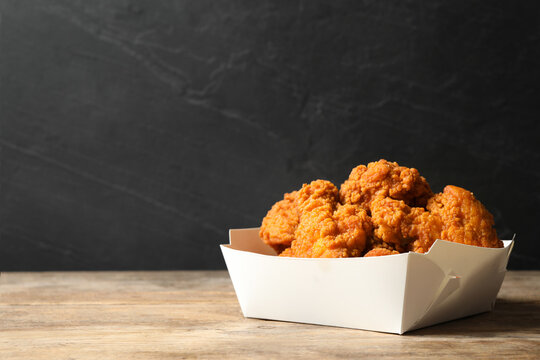 Tasty deep fried chicken pieces on wooden table. Space for text