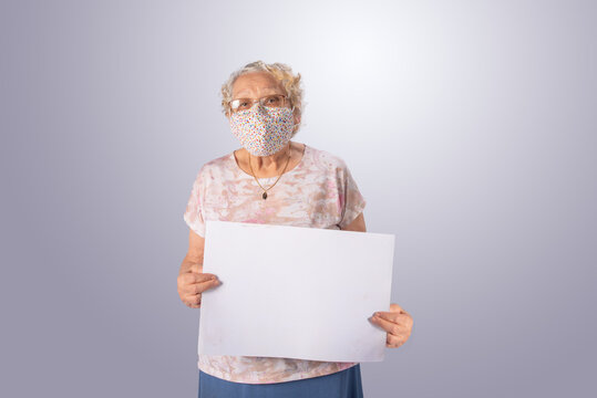 Elderly and masked woman holding a white sign, gray gradient background, selective focus.