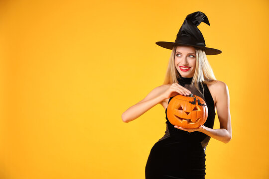 Beautiful woman in witch costume with jack o'lantern on yellow background, space for text. Halloween party