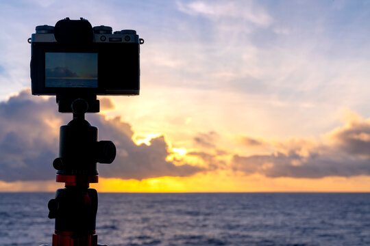 silhouette of mirrorless camera on tripod shooting beautiful calm sea with sunshine reflection on water at sunrise or sunset free copy space for your text