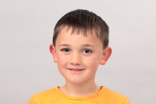 close up portrait of cheerful young 7 or 8 year old boy looking at the camera happy isolated on grey background