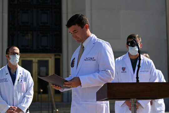 U.S. Navy Commander Dr. Sean Conley, the White House physician, looks at a folder during a briefing about U.S. President Donald Trump's health, in Bethesda