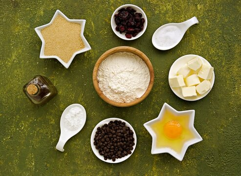 Ingredients for cooking skillet cookie with chocolate chips on an olive green concrete background. Sweets recipes.