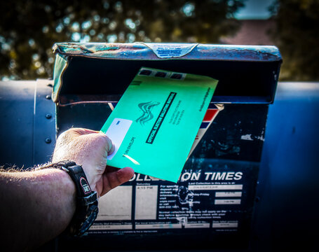 2020_10_02_Tulsa USA Man depositing Official Election Ballot into old banged up drive up mailbox with blurred background