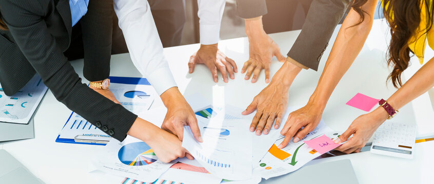 close up Business person reviewing Charts document for business project oworkers Leaning on it in Collective Leap to Find Problem Solutions