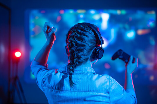 Close-up view from back of emotional gamer girl playing video game at home in front of big screen with joystick and headphone. Colorful neon led lights background. Streamer concept.