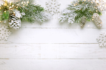 Christmas tree branch with pine cone in snow and retro style clock on a white wooden background....