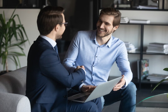 Smiling young male employee shaking hands with pleasant ceo executive manager, making agreement in modern office. Two business partners sitting on comfortable sofa, establishing cooperation.