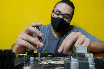 man with chinstrap holding a black screwdriver and with the other hand the motherboard doing technical work Wall mural