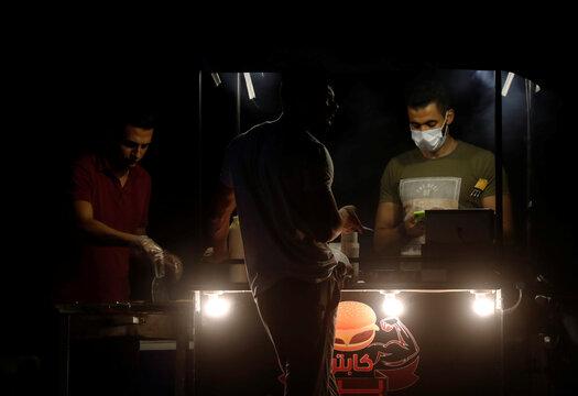 "A street vendor wearing a protective face mask grills burgers at his car ""Captain Burger"", amid the coronavirus disease (COVID-19) pandemic in the Cairo suburb of Maadi"